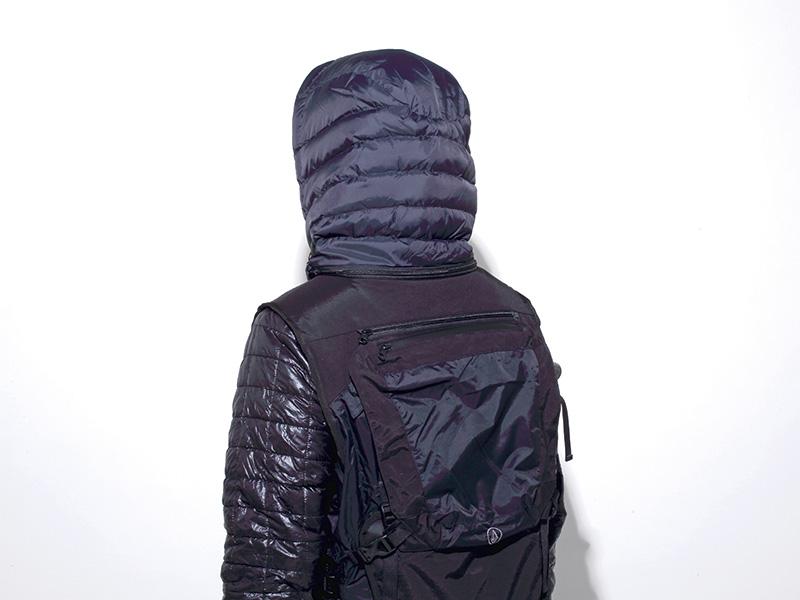 ハイクアップ時の降雪や風から頭部を守る、脱着可能なダウン入りフードが背中のジッパー内に収納されている