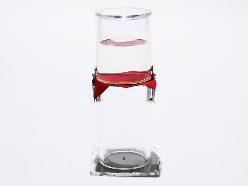 「耐水・防風ボンディングニット」の耐水実験。赤いニット生地を境に上部から下部へ、一滴の水も落ちていないのがわかる。REVOstyleの名に相応しい革新的な素材だ