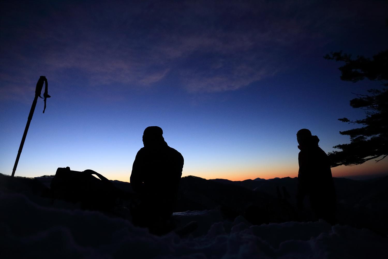 朝6時。すでに3時間暗闇を登り続けて朝焼けのタイミングで休憩