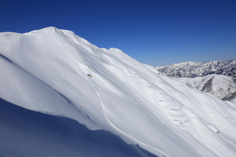 阿部亮介が朝日岳ピークより滑り出して最初にジャンプしたクリフとライン
