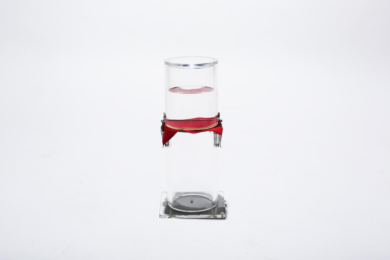 「耐水・防風ボンディングニット」の耐水実験。赤いニット生地を境に上部から下部へ、一滴の水も落ちていないのがわかるREVOstyleの名に相応しい革新的な素材だ