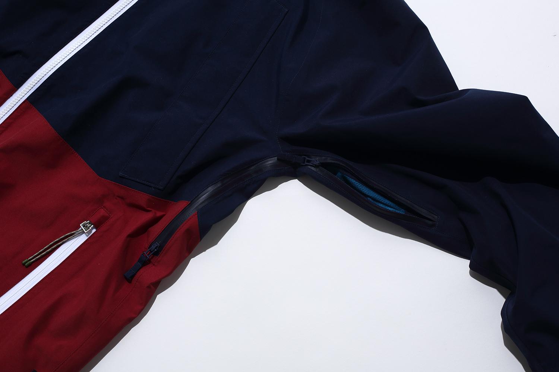 脇の下のジッパーに至るまでYKK® AquaGuard®(止水ジッパー)を採用し、動きやすい。無駄なパーツを省き、軽量化を実現している
