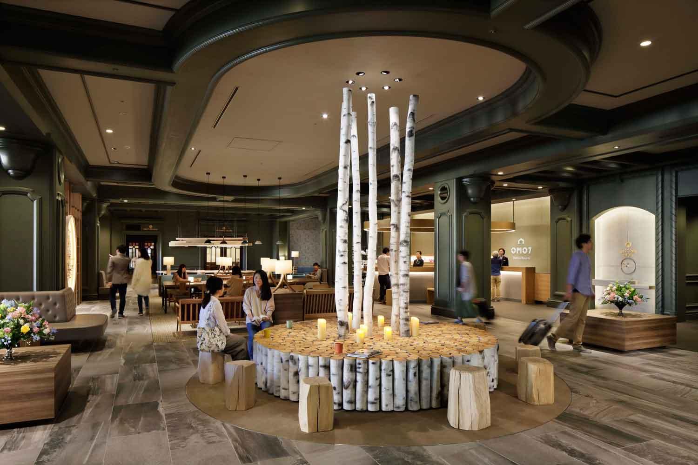 ▲OMOベース 街歩きが楽しくなる仕掛けが詰まったパブリックスペース。北海道の森をイメージした白樺のテーブルが迎えてくれる。家具は国産最高峰とも言われる旭川家具。ランプシェードは、北海道三大ラーメンのひとつ「旭川ラーメン」のどんぶり。高級感と遊び心が心地よくマッチしている。
