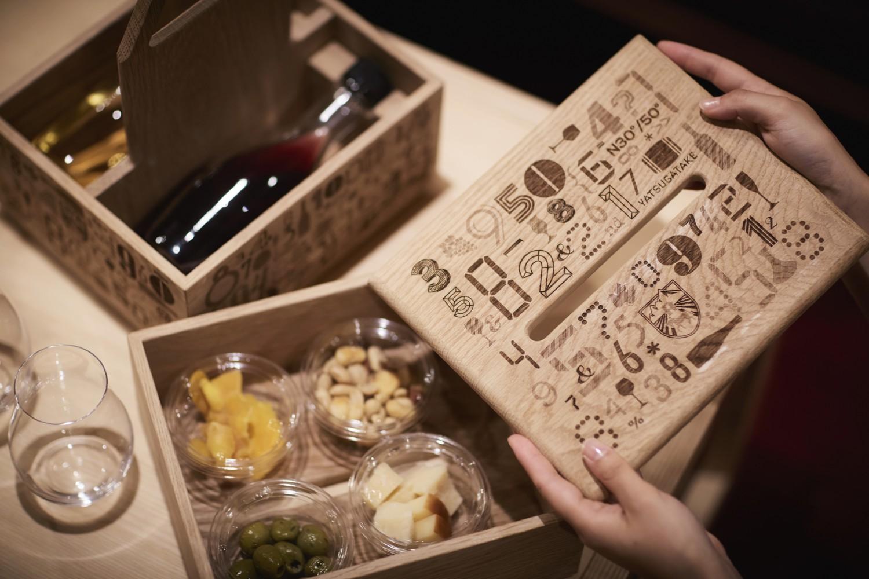▲VINO BOX リゾート内のワインショップ『YATSUGATAKE Wine house』のワインサーバーから、好みのワインを好みの量で部屋にテイクアウトできる『VINO BOX(ヴィノーボックス)』。木箱の下段には小瓶を2本、上段にはナッツやチーズなどのスナックを4種類まで収納できる。