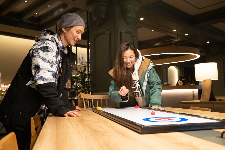 「OMOベース」の奥には旭川家具の大きなテーブルがある。ミニチュアカーリーングを楽しむ二人。